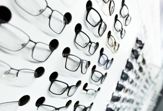 optical store, wall of many fashionable eyeglasses